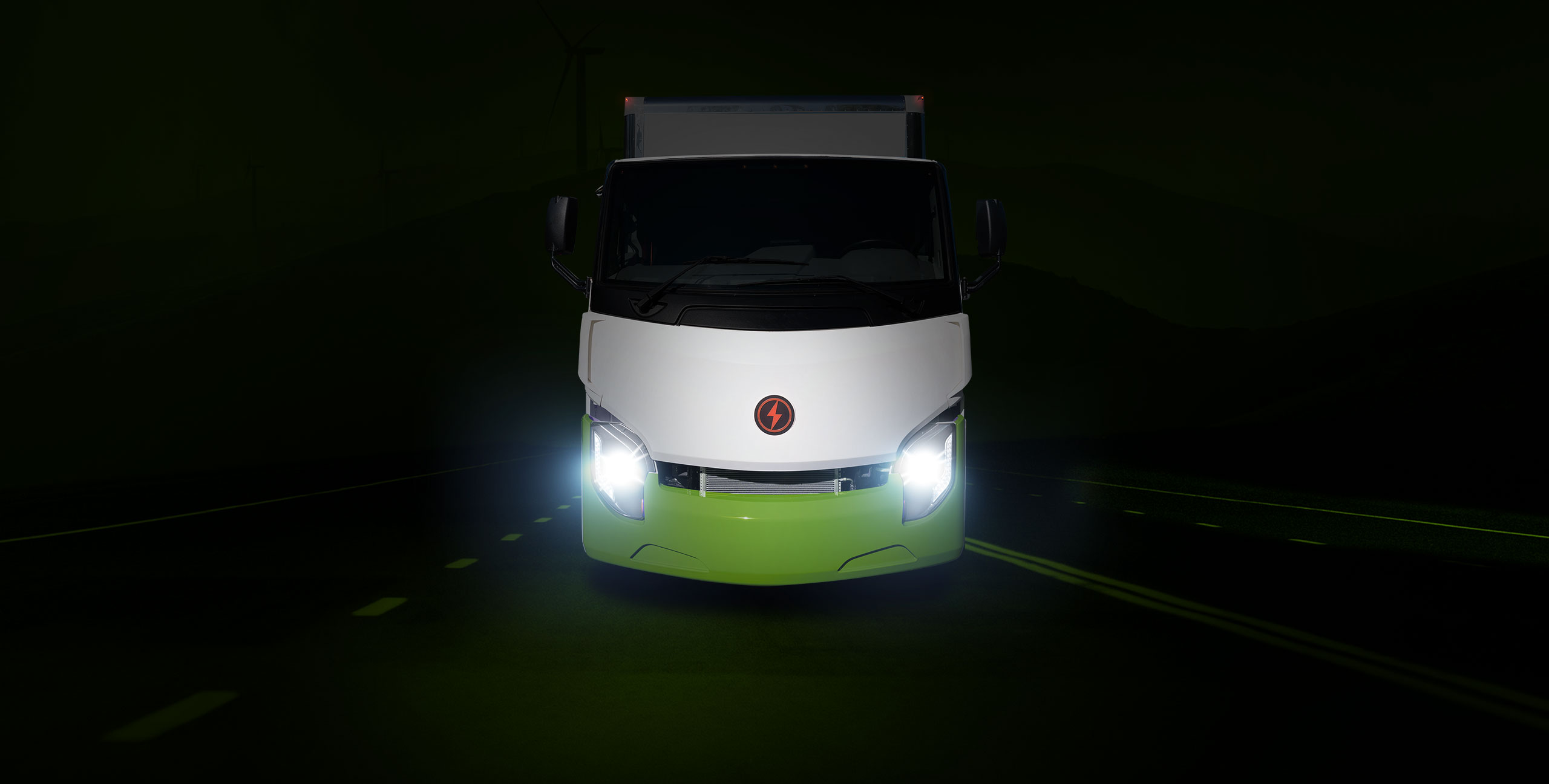 Green and white Lion 8 truck driving forward on road with headlights on
