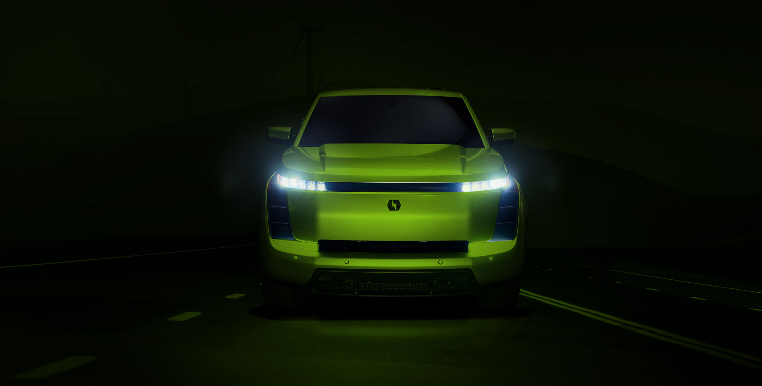 Green Lordstown electric pickup truck driving forward on road with headlights on
