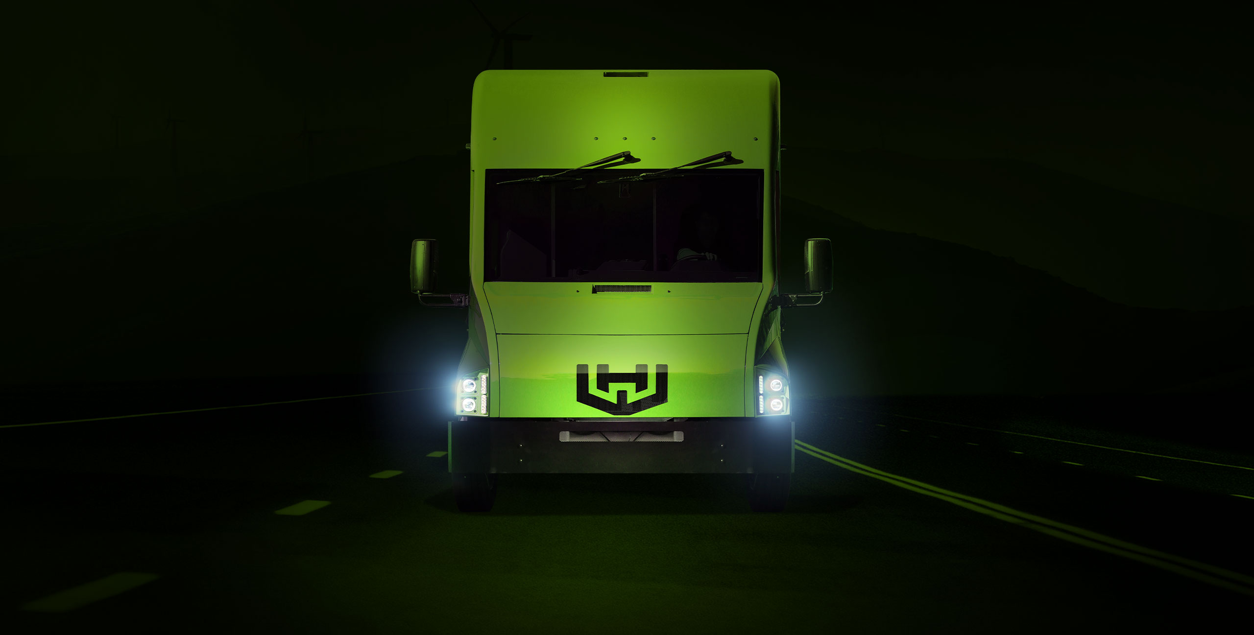 Green Workhorse truck driving forward on road with headlights on
