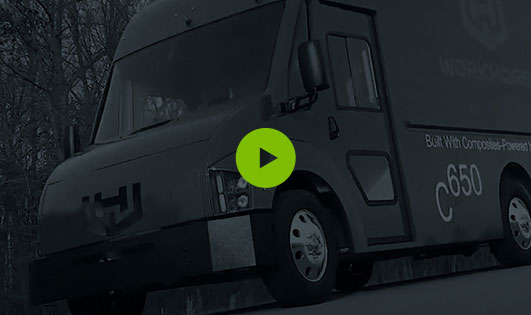 Faded black and white Workhorse C650 van with circular green button in centre for playing Workhorse video